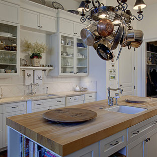 Example of a classic kitchen design in Seattle with glass-front cabinets, wood countertops and white cabinets