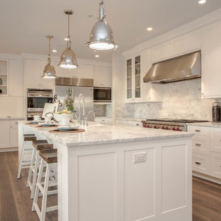 Photo of a country l-shaped kitchen in Seattle with shaker cabinets, white cabinets, marble worktops, white splashback, stainless steel appliances, dark hardwood flooring and marble splashback.