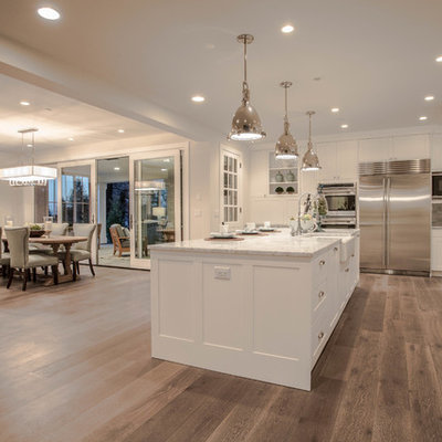 Open concept kitchen - huge farmhouse l-shaped dark wood floor open concept kitchen idea in Seattle with a farmhouse sink, shaker cabinets, white cabinets, marble countertops, white backsplash, stone tile backsplash, stainless steel appliances and an island