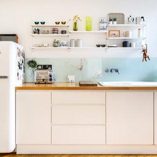 ロンドンの北欧スタイルのおしゃれなI型キッチン (ドロップインシンク、フラットパネル扉のキャビネット、白いキャビネット、木材カウンター、ガラス板のキッチンパネル、無垢フローリング) の写真
