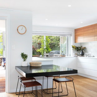 Contemporary u-shaped eat-in kitchen in Wollongong with an undermount sink, flat-panel cabinets, white cabinets, white splashback, stainless steel appliances, medium hardwood floors, brown floor and white benchtop.