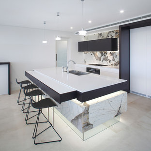 This is an example of a contemporary galley kitchen in Melbourne with with island, a double-bowl sink, flat-panel cabinets, black cabinets, white splashback, beige floor and white benchtop.