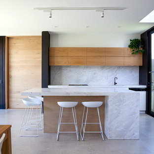 Photo of a mid-sized contemporary eat-in kitchen in Melbourne with with island, flat-panel cabinets, medium wood cabinets, white splashback, concrete floors, grey floor and white benchtop.