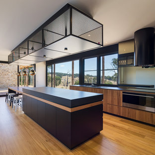 Contemporary galley eat-in kitchen in Melbourne with with island, a drop-in sink, flat-panel cabinets, black cabinets, white splashback, stainless steel appliances, medium hardwood floors, brown floor and black benchtop.