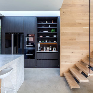Contemporary l-shaped kitchen in Melbourne with with island, flat-panel cabinets, black cabinets, black appliances, concrete floors, grey floor and white benchtop.