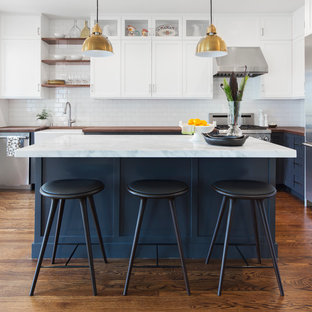 Example of a transitional l-shaped dark wood floor kitchen design in San Francisco with a farmhouse sink, shaker cabinets, white cabinets, wood countertops, white backsplash, subway tile backsplash, stainless steel appliances and an island