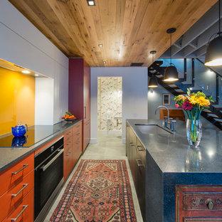 Modelo de cocina de galera, actual, con fregadero bajoencimera, armarios con paneles lisos, puertas de armario rojas, salpicadero amarillo, electrodomésticos con paneles, una isla, suelo gris y encimeras grises
