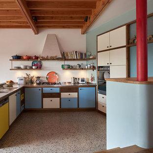 Imagen de cocina en U, retro, de tamaño medio, abierta, con fregadero de doble seno, armarios con paneles lisos, encimera de acero inoxidable, electrodomésticos de acero inoxidable, suelo de madera oscura y suelo marrón