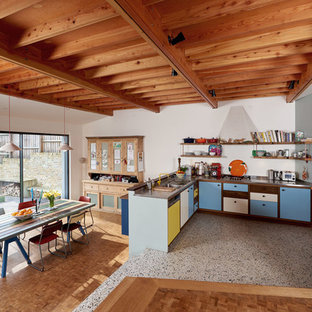 Inspiration for a mid-sized midcentury u-shaped open plan kitchen in London with a double-bowl sink, flat-panel cabinets, stainless steel appliances, medium hardwood floors and brown floor.