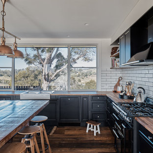 Design ideas for a country l-shaped kitchen in Sunshine Coast with a farmhouse sink, recessed-panel cabinets, black cabinets, wood benchtops, white splashback, subway tile splashback, black appliances, dark hardwood floors, an island, brown floor and brown benchtop.
