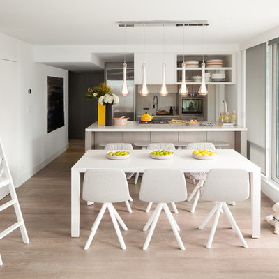 Eat-in kitchen - small scandinavian galley light wood floor eat-in kitchen idea in Vancouver with stainless steel appliances, an undermount sink, flat-panel cabinets, gray cabinets, quartzite countertops, white backsplash, stone slab backsplash and a peninsula