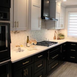 Exempel på ett stort klassiskt kök, med en undermonterad diskho, släta luckor, svarta skåp, bänkskiva i kvarts, vitt stänkskydd, stänkskydd i marmor, svarta vitvaror, vinylgolv, en köksö och grått golv
