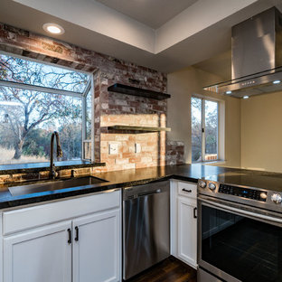 Mid-sized transitional enclosed kitchen appliance - Inspiration for a mid-sized transitional u-shaped dark wood floor and brown floor enclosed kitchen remodel in Other with a triple-bowl sink, recessed-panel cabinets, white cabinets, granite countertops, red backsplash, brick backsplash, stainless steel appliances and a peninsula