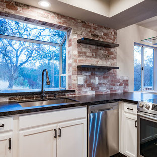 Mid-sized transitional enclosed kitchen inspiration - Example of a mid-sized transitional u-shaped dark wood floor and brown floor enclosed kitchen design in Other with a triple-bowl sink, recessed-panel cabinets, white cabinets, granite countertops, red backsplash, brick backsplash, stainless steel appliances and a peninsula