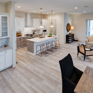 Photo of a mid-sized contemporary single-wall kitchen pantry in Indianapolis with an undermount sink, shaker cabinets, white cabinets, granite benchtops, white splashback, ceramic splashback, white appliances, vinyl floors, with island, multi-coloured floor and white benchtop.