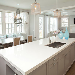 Photo of a coastal open plan kitchen in Minneapolis with a single-bowl sink, engineered stone countertops and grey cabinets.