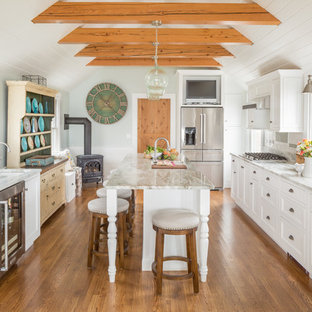 Design ideas for a large country galley separate kitchen in Boston with recessed-panel cabinets, white cabinets, marble benchtops, stainless steel appliances, medium hardwood floors, brown floor, grey splashback, subway tile splashback, with island and an undermount sink.