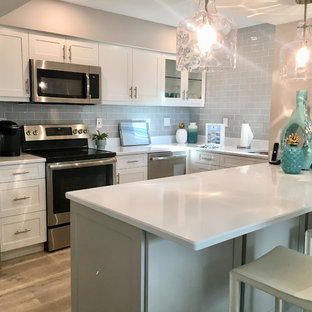 Photo of a small beach style galley eat-in kitchen in Tampa with an undermount sink, shaker cabinets, grey cabinets, quartzite benchtops, glass tile splashback, stainless steel appliances, vinyl floors, a peninsula, grey floor and white benchtop.