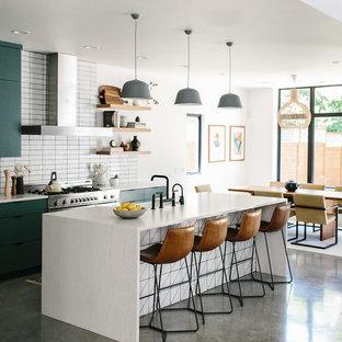 オースティンの中サイズのコンテンポラリースタイルのおしゃれなキッチン (エプロンフロントシンク、フラットパネル扉のキャビネット、緑のキャビネット、珪岩カウンター、白いキッチンパネル、レンガのキッチンパネル、シルバーの調理設備の、コンクリートの床、グレーの床、白いキッチンカウンター) の写真