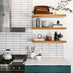 オースティンの中くらいのコンテンポラリースタイルのおしゃれなキッチン (エプロンフロントシンク、フラットパネル扉のキャビネット、緑のキャビネット、珪岩カウンター、白いキッチンパネル、レンガのキッチンパネル、シルバーの調理設備、コンクリートの床、グレーの床、白いキッチンカウンター) の写真