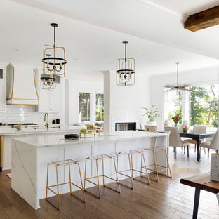 This is an example of a large beach style single-wall open plan kitchen in Minneapolis with white cabinets, quartzite benchtops, white splashback, subway tile splashback, medium hardwood floors, multiple islands, white benchtop, shaker cabinets and brown floor.