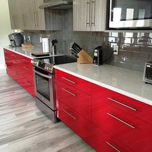 ジャクソンビルの広いエクレクティックスタイルのおしゃれなキッチン (アンダーカウンターシンク、フラットパネル扉のキャビネット、赤いキャビネット、クオーツストーンカウンター、グレーのキッチンパネル、ガラスタイルのキッチンパネル、シルバーの調理設備、磁器タイルの床) の写真