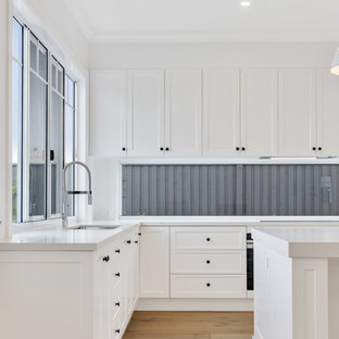 Inspiration for a beach style l-shaped kitchen in Brisbane with an undermount sink, shaker cabinets, white cabinets, window splashback, light hardwood floors, with island, brown floor and white benchtop.