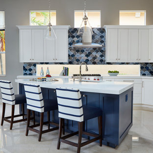Photo of a large beach style l-shaped open plan kitchen in Miami with an undermount sink, shaker cabinets, white cabinets, blue splashback, glass tile splashback, stainless steel appliances, marble floors, with island and beige floor.