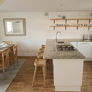 Design ideas for a small coastal u-shaped kitchen/diner in Other with flat-panel cabinets, white cabinets, granite worktops, a breakfast bar, brown floors and grey worktops.