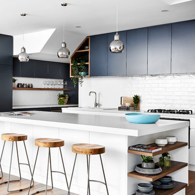 Inspiration for a mid-sized coastal medium tone wood floor kitchen remodel in Sydney with a double-bowl sink, flat-panel cabinets, quartz countertops, white backsplash, an island, white countertops, subway tile backsplash, black cabinets and black appliances