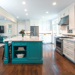 Large beach style u-shaped open plan kitchen in New York with a submerged sink, recessed-panel cabinets, white cabinets, marble worktops, white splashback, metro tiled splashback, stainless steel appliances, plywood flooring, an island, brown floors and white worktops.