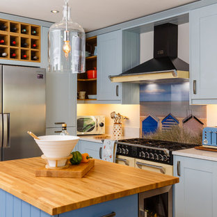 Beach style open concept kitchen photos - Open concept kitchen - beach style u-shaped light wood floor open concept kitchen idea in Cambridgeshire with shaker cabinets, blue cabinets, wood countertops, glass sheet backsplash, paneled appliances, an island and a farmhouse sink