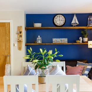 ケンブリッジシャーのビーチスタイルのおしゃれなキッチン (エプロンフロントシンク、シェーカースタイル扉のキャビネット、青いキャビネット、木材カウンター、ガラス板のキッチンパネル、パネルと同色の調理設備、淡色無垢フローリング) の写真