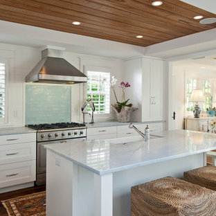 マイアミ, FLのトロピカルスタイルのおしゃれなダイニングキッチン (エプロンフロントシンク、落し込みパネル扉のキャビネット、白いキャビネット、サブウェイタイルのキッチンパネル、シルバーの調理設備の) の写真