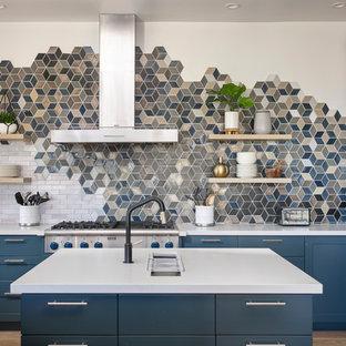 Maritime Küche in L-Form mit Unterbauwaschbecken, Schrankfronten im Shaker-Stil, blauen Schränken, bunter Rückwand, Küchengeräten aus Edelstahl, hellem Holzboden, Kücheninsel und weißer Arbeitsplatte in Sonstige