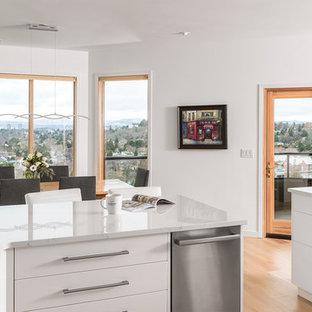 他の地域の中サイズのビーチスタイルのおしゃれなキッチン (アンダーカウンターシンク、フラットパネル扉のキャビネット、濃色木目調キャビネット、クオーツストーンカウンター、青いキッチンパネル、ガラスタイルのキッチンパネル、シルバーの調理設備の、淡色無垢フローリング、黄色い床、白いキッチンカウンター) の写真