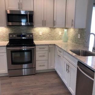 ニューヨークの中サイズのビーチスタイルのおしゃれなキッチン (アンダーカウンターシンク、シェーカースタイル扉のキャビネット、白いキャビネット、珪岩カウンター、青いキッチンパネル、ガラスタイルのキッチンパネル、シルバーの調理設備の、ラミネートの床、アイランドなし、グレーの床、緑のキッチンカウンター) の写真