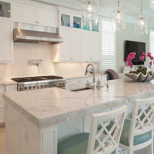 Large transitional l-shaped open plan kitchen in Miami with white splashback, with island, a farmhouse sink, shaker cabinets, white cabinets, marble benchtops, porcelain splashback, stainless steel appliances, marble floors and beige floor.