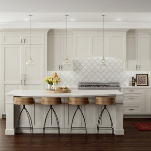This is an example of a medium sized traditional l-shaped kitchen/diner in Providence with raised-panel cabinets, white cabinets, composite countertops, white splashback, terracotta splashback, stainless steel appliances, dark hardwood flooring, an island, a submerged sink and brown floors.