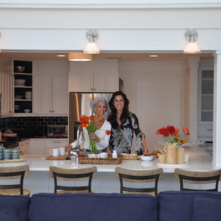 Photo of a large beach style u-shaped eat-in kitchen in Orlando with a farmhouse sink, shaker cabinets, white cabinets, quartz benchtops, blue splashback, ceramic splashback, stainless steel appliances, ceramic floors and a peninsula.