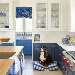Diseño de cocina costera, grande, con puertas de armario azules, salpicadero blanco, salpicadero de azulejos de cerámica, una isla, fregadero bajoencimera, armarios con paneles con relieve, electrodomésticos de acero inoxidable, suelo de madera clara y suelo beige