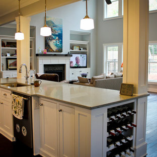 This is an example of a mid-sized beach style galley open plan kitchen in Raleigh with shaker cabinets, white cabinets, with island, an undermount sink, glass tile splashback, white appliances and dark hardwood floors.