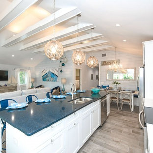 Design ideas for a beach style eat-in kitchen in Tampa with an undermount sink, shaker cabinets, white cabinets, quartzite benchtops, blue splashback, glass tile splashback, stainless steel appliances, porcelain floors, with island, grey floor and blue benchtop.