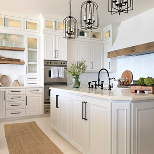 Photo of a nautical u-shaped kitchen in San Diego with raised-panel cabinets, white cabinets, white splashback, stainless steel appliances, an island, beige floors and beige worktops.