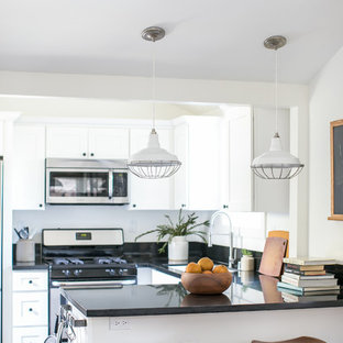 Photo of a small country u-shaped open plan kitchen in Orange County with an undermount sink, shaker cabinets, white cabinets, granite benchtops, black splashback, stainless steel appliances, vinyl floors and a peninsula.