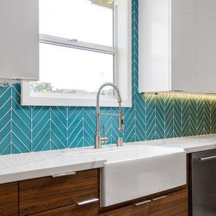 ロサンゼルスの広いモダンスタイルのおしゃれなキッチン (エプロンフロントシンク、フラットパネル扉のキャビネット、白いキャビネット、クオーツストーンカウンター、青いキッチンパネル、ガラスタイルのキッチンパネル、シルバーの調理設備、磁器タイルの床、グレーの床、白いキッチンカウンター) の写真