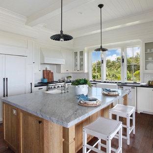 ハワイのトロピカルスタイルのおしゃれなキッチン (エプロンフロントシンク、シェーカースタイル扉のキャビネット、白いキャビネット、白いキッチンパネル、パネルと同色の調理設備、無垢フローリング、茶色い床、グレーのキッチンカウンター) の写真