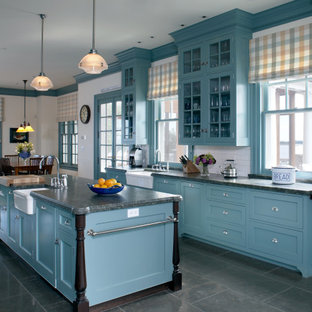 This is an example of a beach style kitchen in Boston with recessed-panel cabinets, blue cabinets, red splashback and green benchtop.