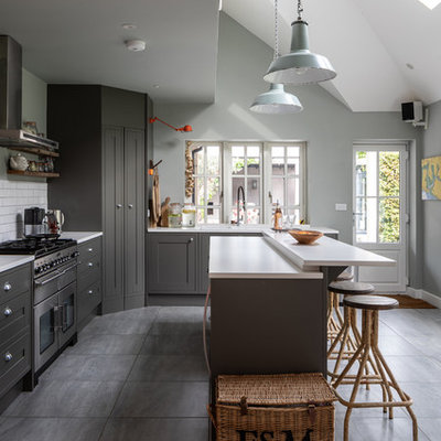 Example of a mid-sized beach style l-shaped gray floor kitchen design in Sussex with a double-bowl sink, gray cabinets, white backsplash, stainless steel appliances, an island, white countertops, shaker cabinets and subway tile backsplash