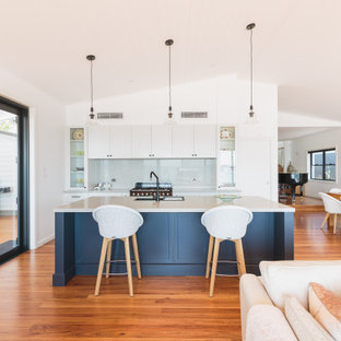 Photo of a large beach style open plan kitchen in Newcastle - Maitland with shaker cabinets, white cabinets, quartz benchtops, grey splashback, with island, white benchtop, an undermount sink, medium hardwood floors and vaulted.